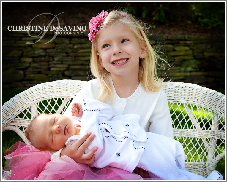 Beautiful blonde girl holding newborn baby brother.