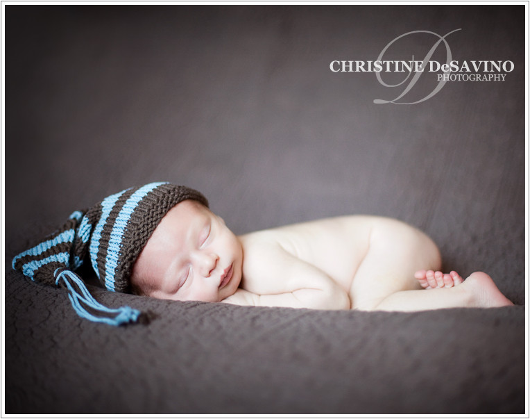 Beautiful newborn boy with knit hat lying on brown blanket