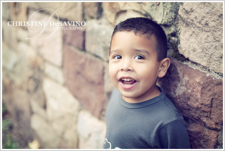 Beautiful boy leans against a stone wall - NJ Children's Photographer