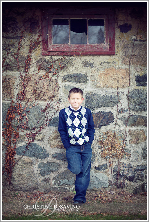 Boy leans against beautiful stone wall with broken window - NY Children's Photographe