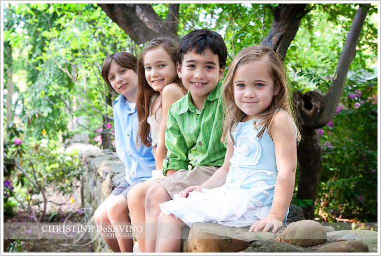 Family of four sits on stone wall - NJ Family Photographer