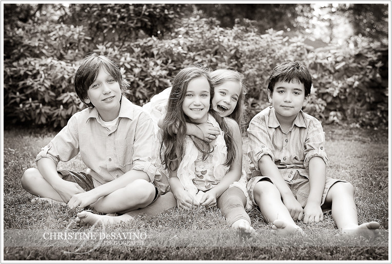Black and white of four siblings on grass - NJ Family Photographer