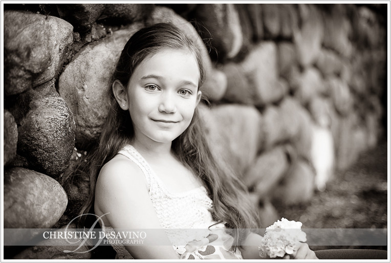 Black and whit of girl sitting against stone wall - NJ Child Photographer